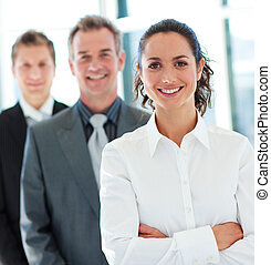 Smiling young businesswoman in front of her team
