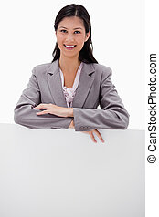 Smiling young businesswoman leaning on blank wall