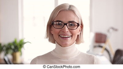 Smiling young businesswoman looking at camera in office, closeup portrait