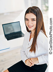 Smiling young businesswoman posing in a modern office