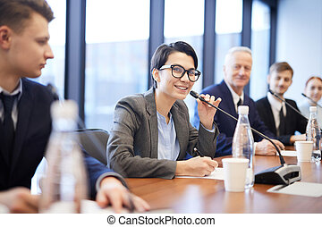Smiling Young Businesswoman Speaking at Conference