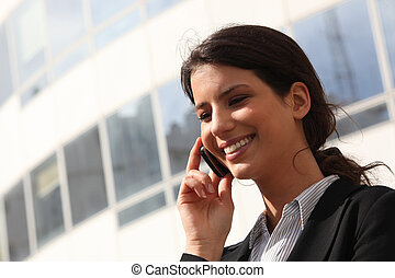 Smiling young businesswoman using a cellphone