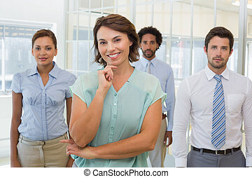 Smiling young businesswoman with colleagues in office
