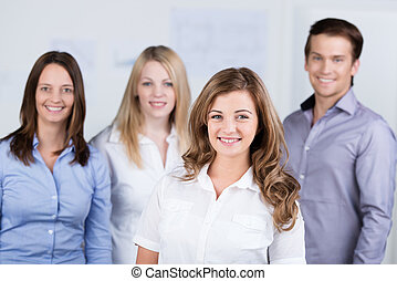 Smiling young businesswoman with her colleagues