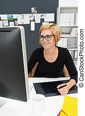 Smiling young businesswoman working at a desk