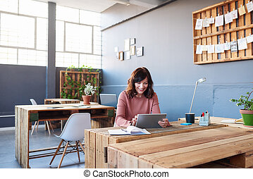 Smiling young businesswoman working on a tablet in an office