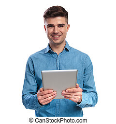 smiling young casual man holding a tablet