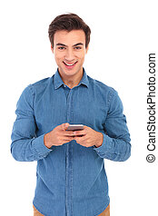 smiling young casual man texting on his mobile phone