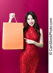 smiling young chinese woman with showing shopping bags