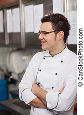 smiling young cook with folded arms standing in the kitchen