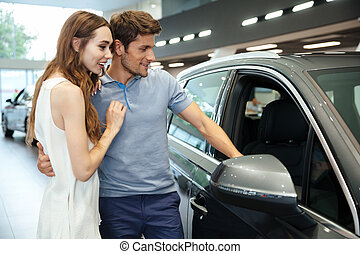 Smiling young couple choosing a car at the dealership