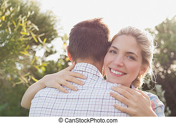Smiling young couple embracing in park