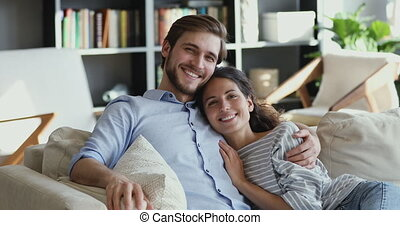 Smiling young couple hugging on comfortable couch looking at camera