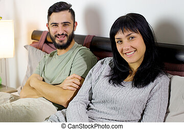 Smiling young couple in bed looking