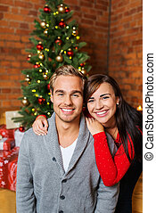 Smiling Young Couple in Front Christmas Tree