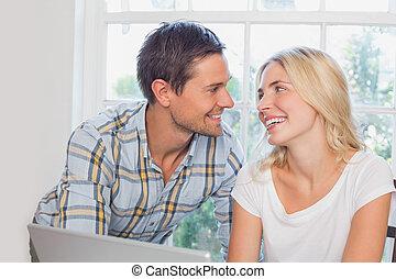 Smiling young couple looking at each other at home