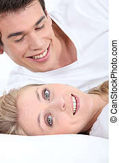 Smiling young couple lying down