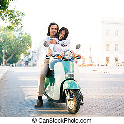 Smiling young couple on scooter