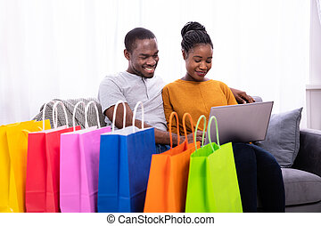 Smiling Young Couple Shopping On Laptop