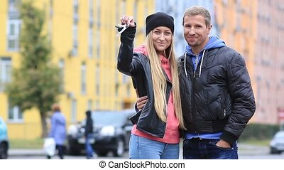 Smiling young couple showing keys of new house