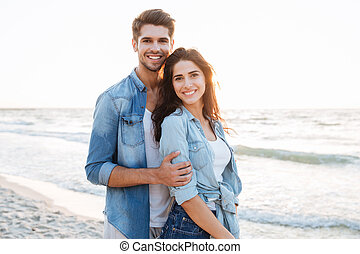 Smiling young couple standing at the beach