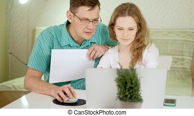 Smiling young couple using laptop at home emotionally discuss