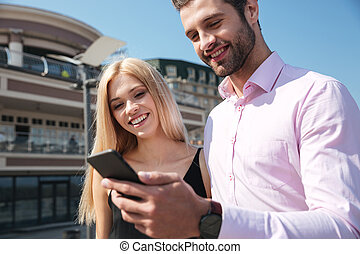 Smiling young couple using mobile phone