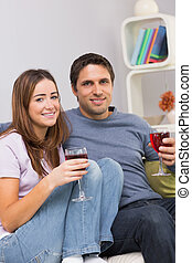 Smiling young couple with wine glasses sitting at home