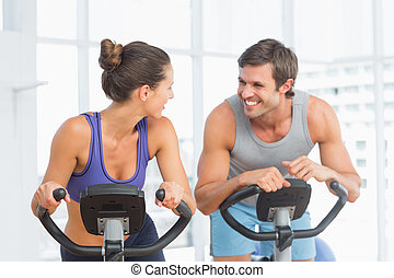 Smiling young couple working out at spinning class - Smiling...