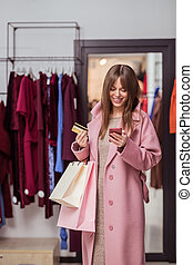 Smiling young customer with a credit card