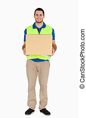 Smiling young delivery man carrying a parcel against a white...