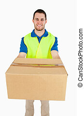 Smiling young delivery man handing over parcel
