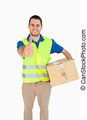 Smiling young delivery man with parcel giving thumb up