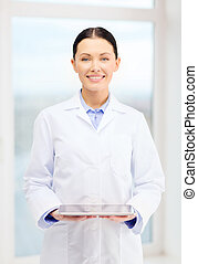 smiling young doctor with tablet pc in cabinet