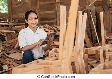 smiling young entrepreneur looking at the camera while using a tablet
