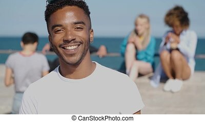 Smiling young ethnic man in sunshine