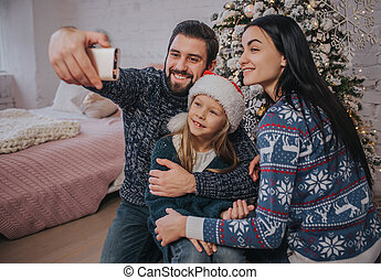 Smiling young family in Christmas atmosphere making photo with smartphone