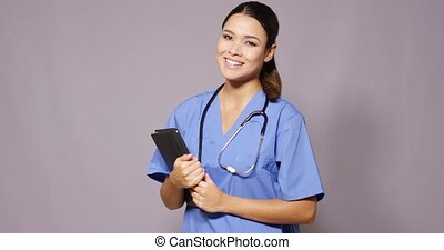 Smiling young female doctor in scrubs - Smiling young female...