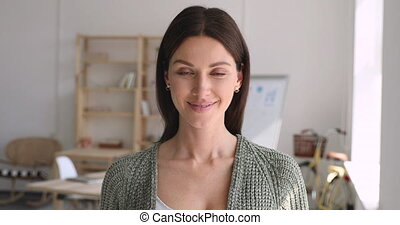 Smiling young female entrepreneur looking at camera posing in office