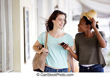 Smiling young female friends walking and talking