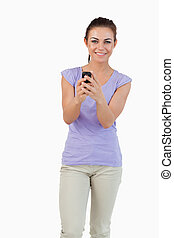 Smiling young female holding her cellphone