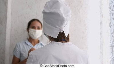 Smiling young female patient with female doctor in white uniform thanking for help or feeling excited about healthcare treatment results at meeting.