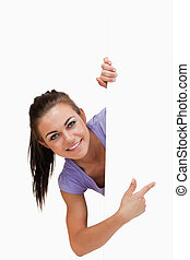 Smiling young female pointing around the corner against a...