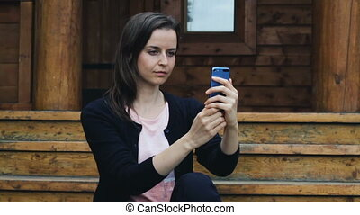 Smiling young female posing to take a selfie outdoors