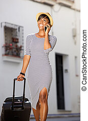 Smiling young female traveler walking with cell phone and suitcase