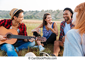 Smiling young friends drinking beer and playing guitar outdoors