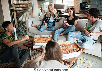 Smiling young friends eating pizza and talking at home -...