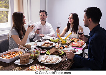 Friends Enjoying Food With Glass Of Wine