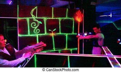 Group of adult people with laser guns having fun on dark lasertag arena