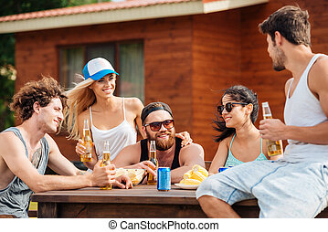 Smiling young friends sitting and drinking beer outdoors